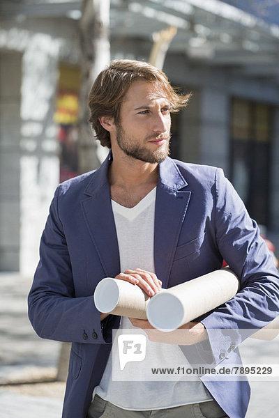 Architekt mit Papierrollen