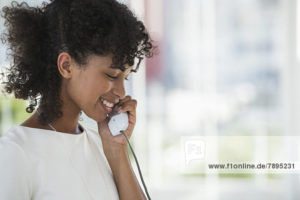 Nahaufnahme einer Frau am Festnetztelefon