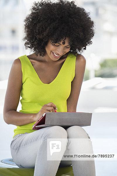 Lächelnde Frau mit einem digitalen Tablett