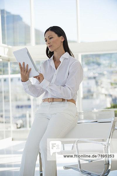 Geschäftsfrau  die ein digitales Tablett benutzt  während sie auf einem Tisch in einem Büro sitzt.