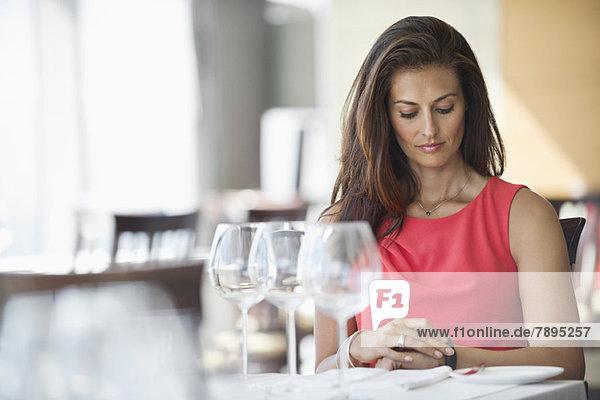 Frau sitzt in einem Restaurant und schaut auf die Armbanduhr.