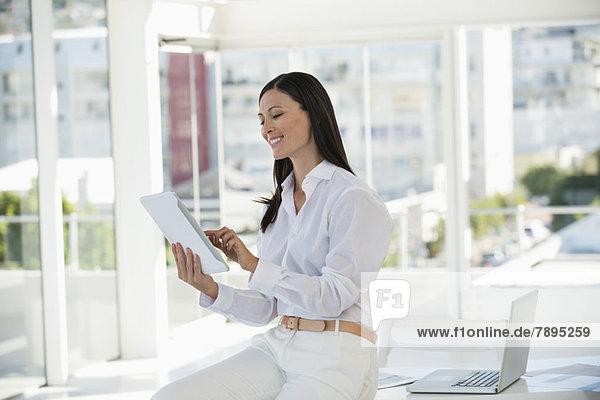 Geschäftsfrau mit einem digitalen Tablett und einem Lächeln im Büro
