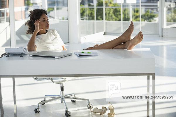 Frau  die zu Hause auf einem Stuhl sitzt und nachdenkt.