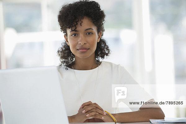 Porträt einer Frau  die vor einem Laptop sitzt