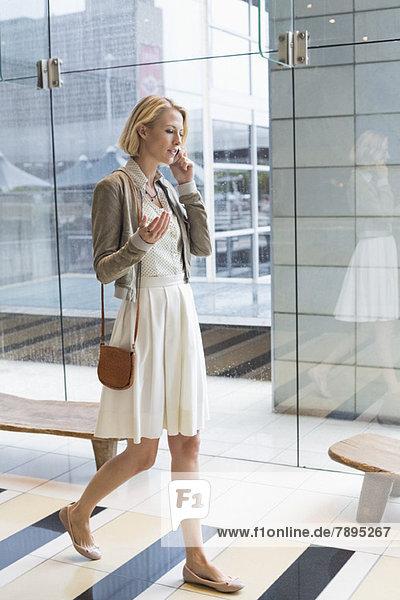 Frau  die auf einem Handy spricht  während sie auf einem Flughafen spazieren geht.