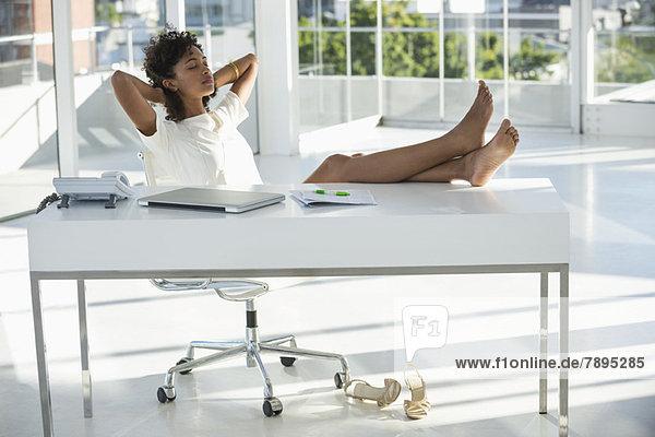 Frau entspannt sich zu Hause auf einem Stuhl
