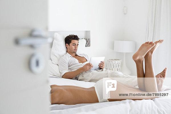 Frau in Dessous auf dem Bett liegend und Mann beim Lesen eines digitalen Tabletts