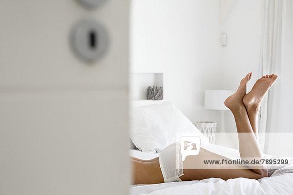 Flachschnittansicht einer auf dem Bett liegenden Frau in Unterwäsche