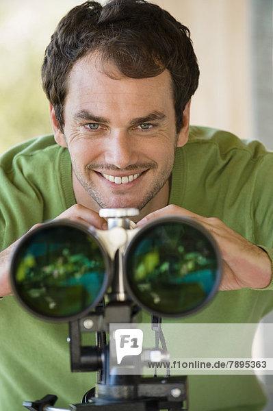 Lächelnder Mann schaut durchs Fernglas