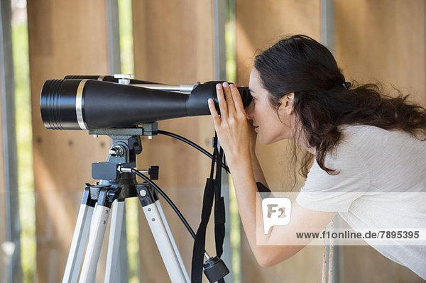 Frau schaut durchs Fernglas auf Stativ