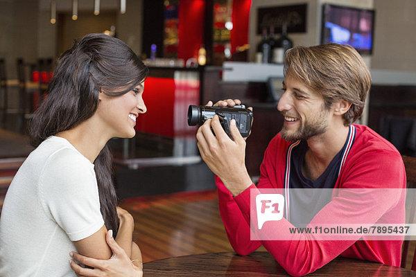 Mann filmt seine Freundin mit einer Heimvideokamera