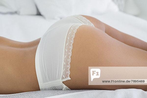 Mittelteilansicht einer auf dem Bett liegenden Frau in Unterwäsche