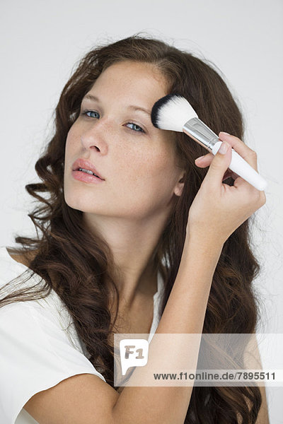 Frau beim Schminken mit Schminkpinsel