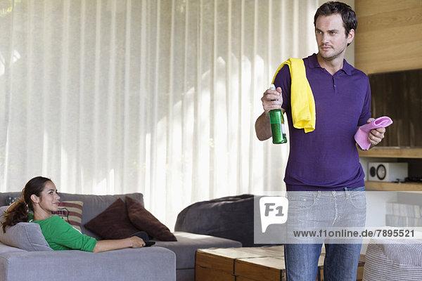 Mann mit Reinigungsgerät und seiner Frau auf dem Sofa