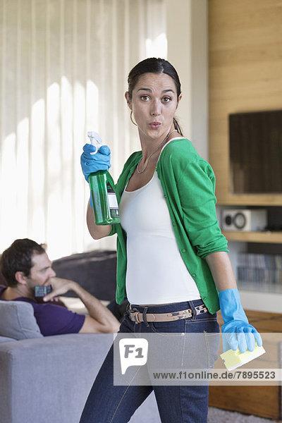 Frau hält Reinigungsgeräte in der Hand  ihr Mann sitzt auf einer Couch