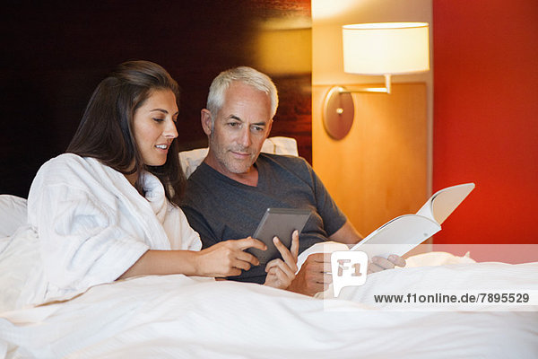 Paar betrachtet ein digitales Tablett in einem Hotelzimmer