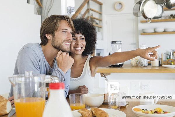 Lächelndes Paar am Esstisch sitzend
