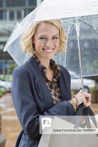 Porträt einer lächelnden Frau mit Regenschirm