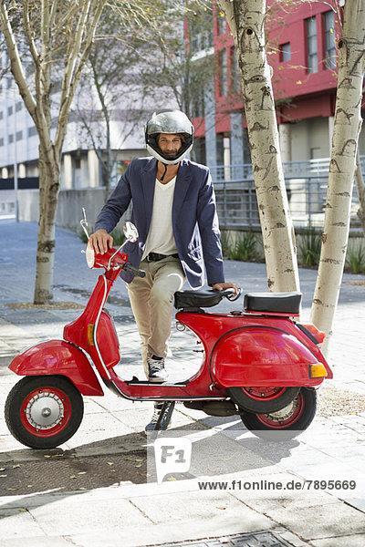 Porträt eines Mannes  der mit seinem Roller steht
