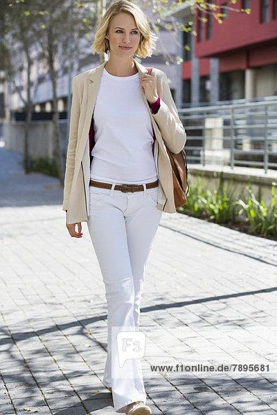 Frau geht auf der Straße und lächelt.