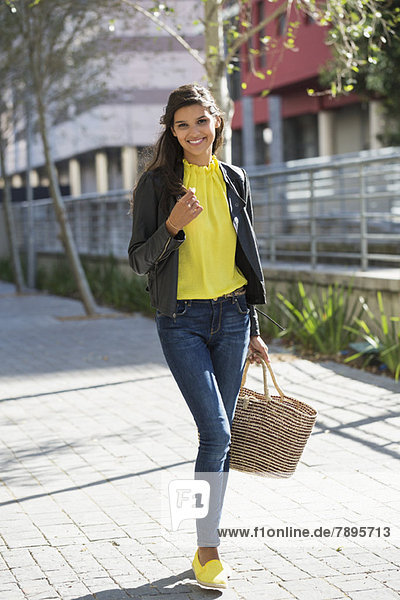 Porträt einer Frau  die mit einer Handtasche unterwegs ist.