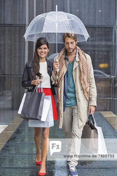 Paar mit Einkaufstaschen  die bei Regen unter einem Regenschirm geschützt sind