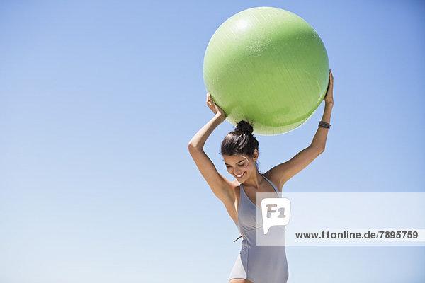 Schöne Frau mit einem Fitnessball am Strand