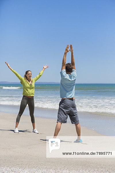 Frau und ihr Trainer beim Training am Strand