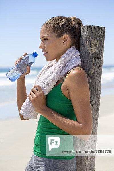 Frau lehnt sich an einen Holzpfosten am Strand und trinkt Wasser.