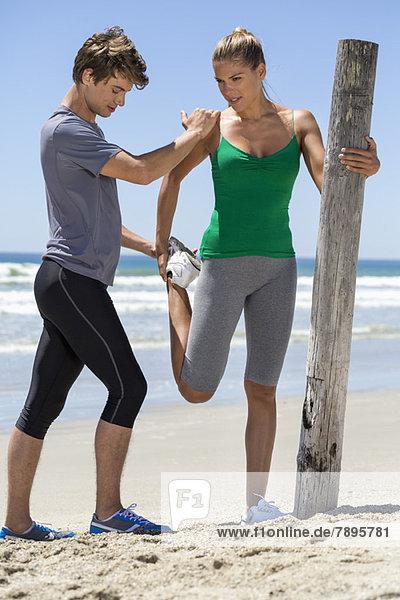 Mann  der einer Frau hilft  sich am Strand zu bewegen.