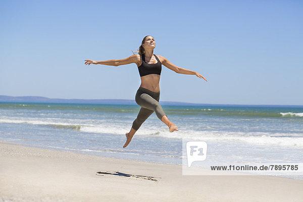 Frau beim Springen am Strand