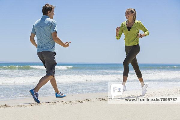 Frau beim Joggen am Strand mit ihrem Trainer