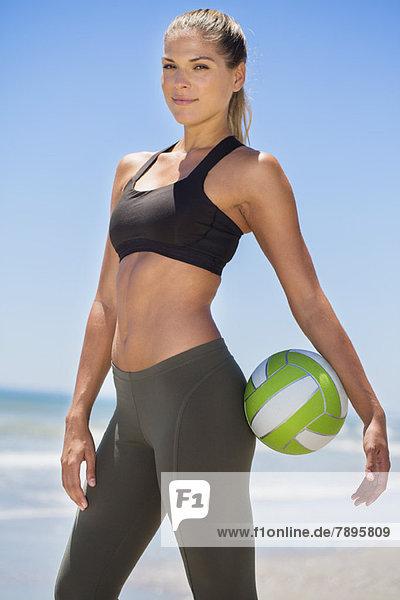Porträt einer Frau  die einen Volleyball hält