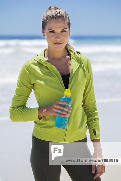 Frau mit einer Wasserflasche am Strand