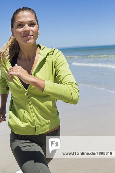 Porträt einer am Strand laufenden Frau