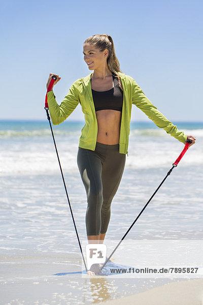 Lächelnde Frau beim Training mit einem Brust-Expander am Strand