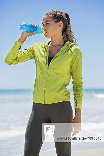 Frau trinkt Wasser am Strand