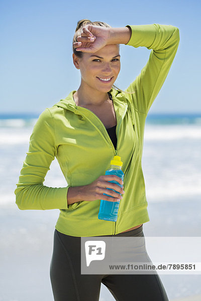 Lächelnde Frau mit einer Wasserflasche am Strand