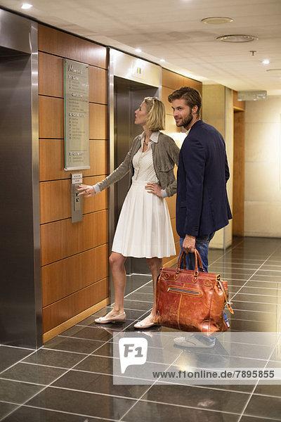 Paar steht vor einem Aufzug auf einem Flughafen