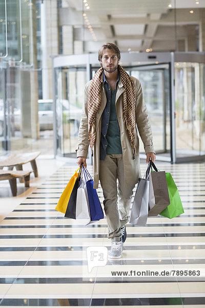 Portrait eines Mannes mit Einkaufstaschen