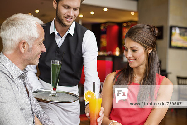 Waiter serving drinks to a couple in a restaurant