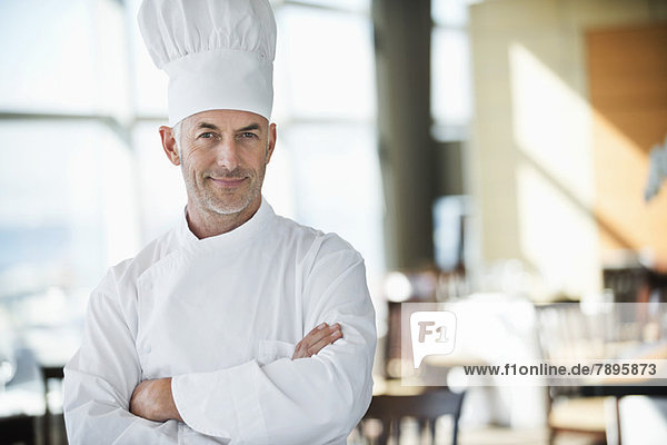 Portrait of a chef smiling with arms crossed in a restaurant