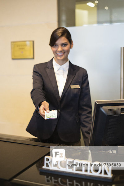Receptionist holding a key card and smiling at the hotel reception counter