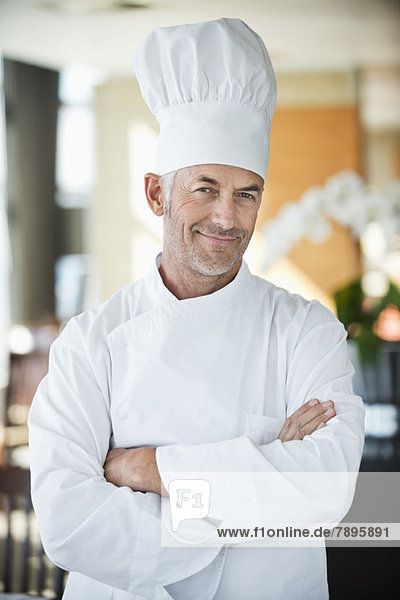 Porträt eines Küchenchefs  der mit gekreuzten Armen lächelt