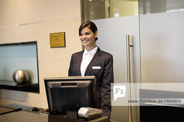 Rezeptionistin steht an der Rezeption des Hotels und lächelt