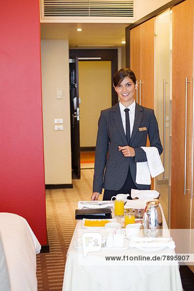 Porträt der lächelnden Kellnerin mit Zimmerservicetisch im Hotelzimmer