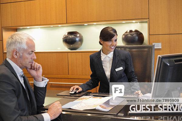 Rezeptionist bei der Arbeit an einem Desktop-PC mit einem Geschäftsmann an der Hotelrezeption
