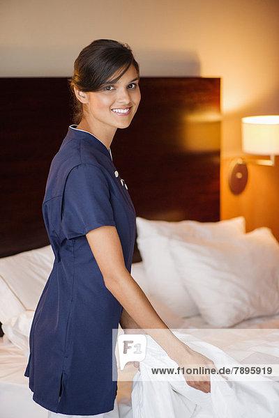 Porträt eines Mädchens  das lächelt  während es ein Bett in einem Hotelzimmer macht.