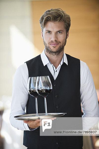 Porträt eines Kellners  der ein Tablett mit Weingläsern in einem Restaurant hält.