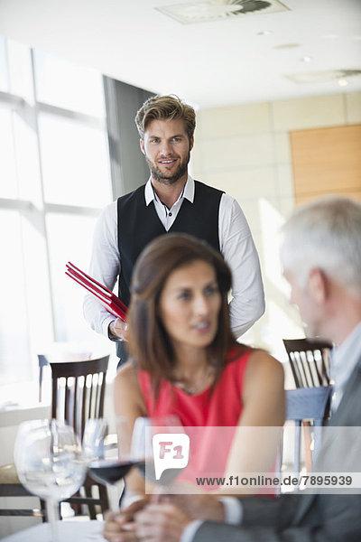 Paar genießt Rotwein in einem Restaurant mit Kellner im Hintergrund